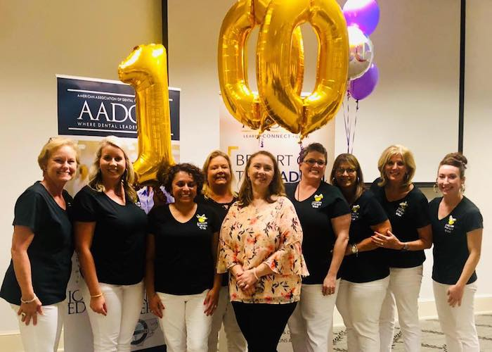 A group of AADOM members celebrating with balloons that say 100