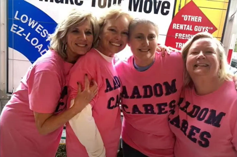 four women wearing our AADOM Cares shirts and smiling